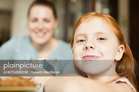 Girl with a milk moustache at dining room table - p1427m2283158 by Roberto Westbrook