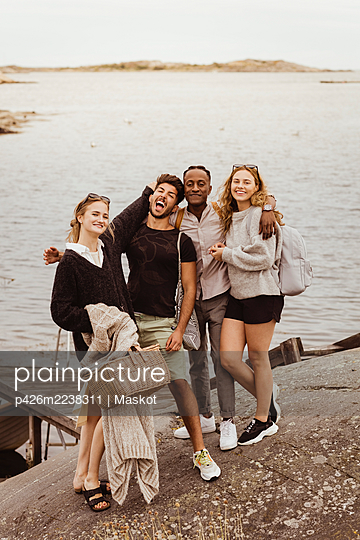 Portrait of smiling friends standing against sea during summer vacation - p426m2238311 by Maskot