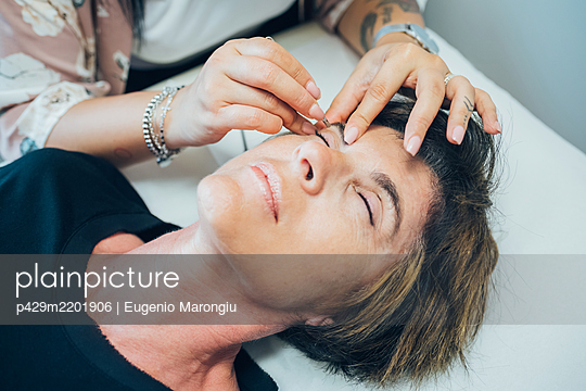 Woman getting her eyebrows done in a beauty salon. - p429m2201906 by Eugenio Marongiu