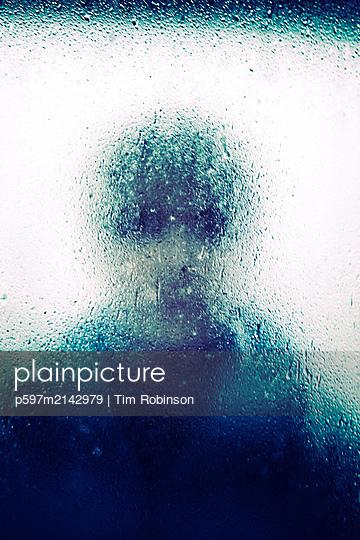 Woman looking at camera through rain splattered window - p597m2142979 by Tim Robinson