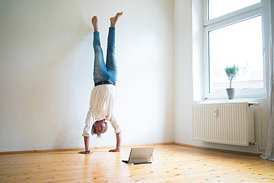 Mature man doing a handstand on floor in empty room looking at tablet - p300m1562281 by Robijn Page
