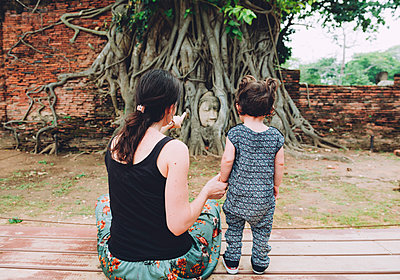 Thailand, Ayutthaya, Mother and daughter visiting the Buddha head in between tree roots at Wat Mahathat - p300m2058796 von Gemma Ferrando