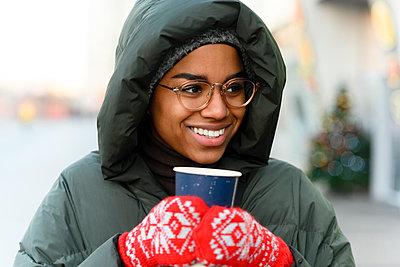 Smiling woman with reusable cup wearing gloves in winter - p300m2282897 by Katharina und Ekaterina