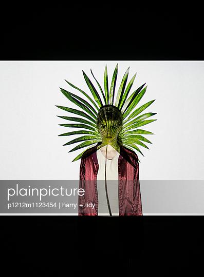 Projektion Palmblatt auf junge Frau mit Blick in Kamera - p1212m1123454 von harry + lidy