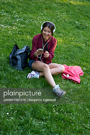 Young woman with headphones sitting on a meadow using cell phone - p300m1587476 von Benjamin Egerland