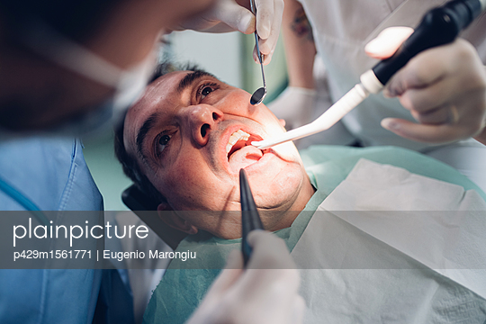 plainpicture - plainpicture p429m1561771 - Dentist looking into male p... - plainpicture/Cultura/Eugenio Marongiu