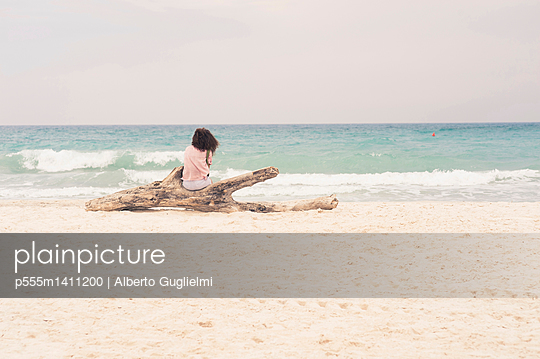 Woman sunbathing on driftwood log on beach - p555m1411200 by Alberto Guglielmi