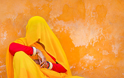 Woman wearing red and yellow sari and veil covering her head sitting on floor, leaning against orange wall. - p1100m1570948 by Mint Images
