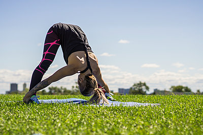 Young female athlete doing yoga and using her flexibility outdoors - p1362m2111565 by Charles Knox