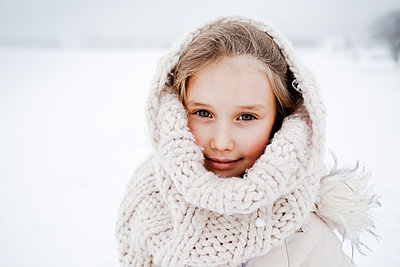 Small girl covered with knitted scarf during winter - p300m2256092 by Katharina Mikhrin