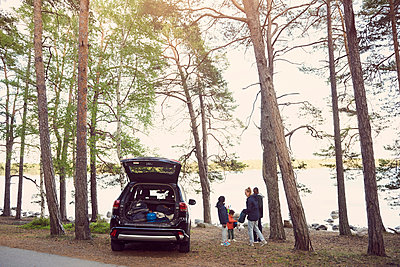 Family standing by car amidst trees during camping at beach - p426m1507216 by Maskot