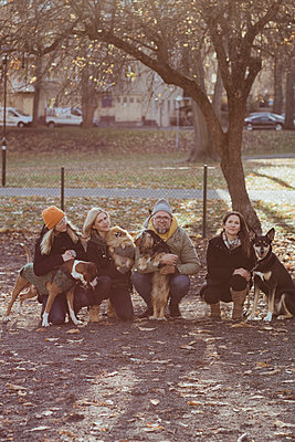 Portrait of man and women crouching with dogs at park during autumn - p426m2194959 by Maskot