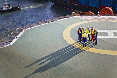 Workers talking on helipad of oil rig - p42915046f by Hybrid Images