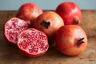 Whole and halved pomegranates - p429m757557f by Danielle Wood