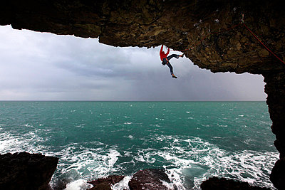 A climber scales cliffs near Swanage, Dorset, England, United Kingdom, Europe - p871m805703 by David Pickford