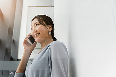 Germany, Bavaria, Munich, Businesswoman talking on smart phone - p924m2271303 by suedhang photography