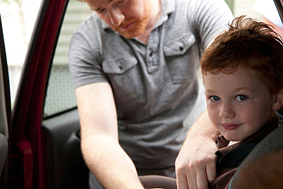 Father securing son in car - p924m700357 by Flynn Larsen