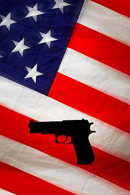 Hand gun against US flag - p975m2287891 by Hayden Verry