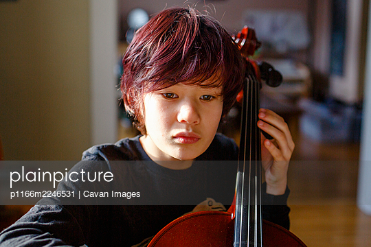 A boy with intense focus and dyed red hair plays cello in window light - p1166m2246531 by Cavan Images
