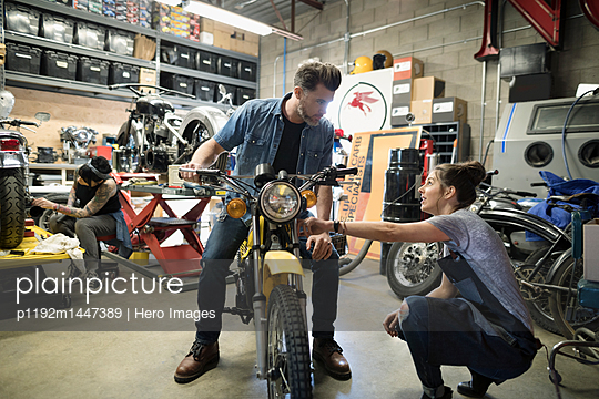 Motorcycle mechanics talking, fixing motorcycle in auto repair shop