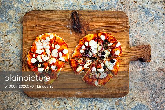 Selbstgebackene Pizza auf Holzbrett - p1386m2026378 von Lindqvist
