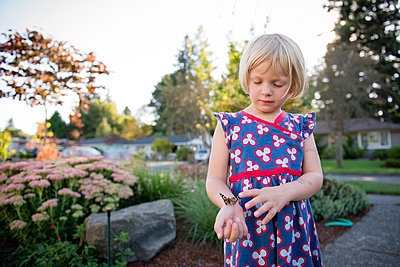 Girl with butterfly standing by plants against sky at park - p1166m1555033 by Cavan Images