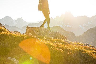 Lower half of backpacker hiking on mountain ridge - p1166m2212411 by Cavan Images