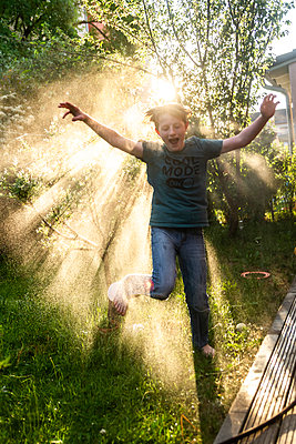 Boy having fun with garden hose - p300m1588101 von Sandra Roesch