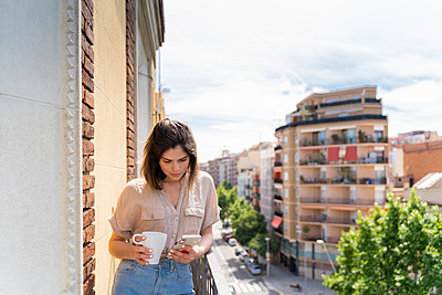 Young woman on balcony in the city using cell phone - p300m2113913 von VITTA GALLERY