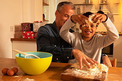 Father and son kneading dough on table while sitting in kitchen - p300m2243992 by Pete Muller