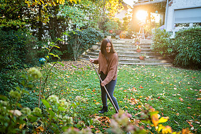 Happy woman sweeping garden with broom in back yard - p300m2253210 by Annika List
