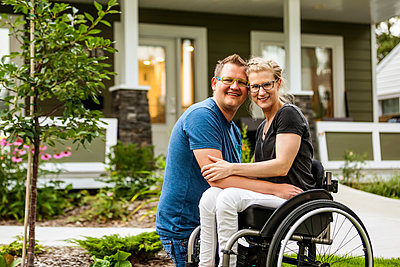A husband and his paraplegic wife posing for a family photo in their front yard on a warm fall day: Edmonton, Alberta, Canada - p442m2177318 by LJM Photo