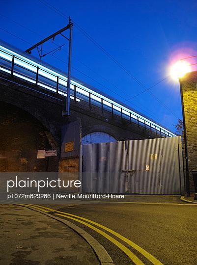 Speeding train passing over road - p1072m829286 by Neville Mountford-Hoare