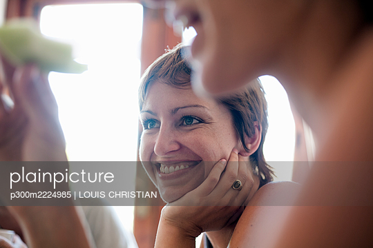 Smiling female with hand on chin sitting by friend in restaurant - p300m2224985 by LOUIS CHRISTIAN