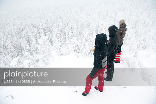 Caucasian hikers on mountaintop admiring snowy forest - p555m1410835 by Aleksander Rubtsov