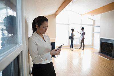 Realtor using smart phone, showing new house to young couple - p1192m1559972 by Hero Images