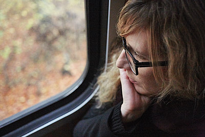 Young woman looking out train window - p1198m2168763 by Guenther Schwering