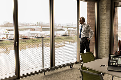 Serious mature businessman standing at the window looking out - p300m1563071 by Uwe Umstätter