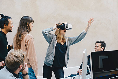 Female computer programmer using VR glasses while standing with colleagues in office - p426m1494003 by Maskot