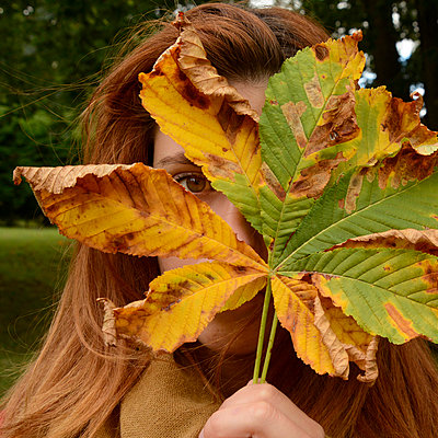 Young woman behind a leaf - p813m899993 by B.Jaubert