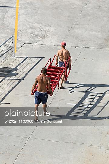 Zwei Männer tragen eine rote Leiter - p1292m1169360 von Niels Schubert
