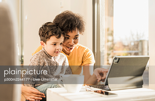 Woman teaching boy through digital tablet while sitting at home - p300m2244177 by Uwe Umstätter