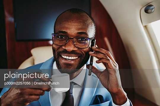 Happy businessman with coffee cup talking on smart phone in private jet - p300m2257056 by OneInchPunch