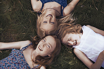 Portrait happy sisters laying in grass - p1023m2088075 by Arman Zhenikeyev