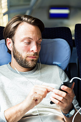 Mann hört im Zug Musik - p1114m1159791 von Carina Wendland