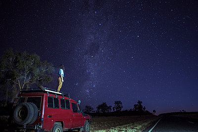 Woman looking at star field while standing on car roof at desert - p1166m1519074 by Cavan Images