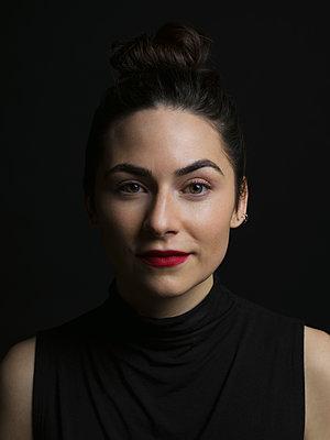 Portrait confident brunette woman against black background - p1192m1403538 by Hero Images