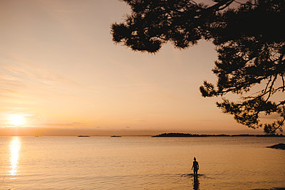 Woman bathing in sea at sunset - p312m2146197 by Stina Gränfors