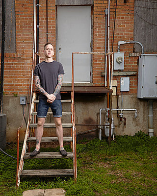 Portrait of young tattooed man standing on staircase - p429m802537 by Cultura
