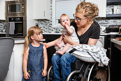A paraplegic mom in a wheelchair talking with her daughter and holding her baby in her lap while working in her kitchen; Edmonton, Alberta, Canada - p442m2155047 by LJM Photo